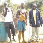 Chairman of the Newton Amputee and War Victims Camp with some of the men helping to mold blocks for the orphanage