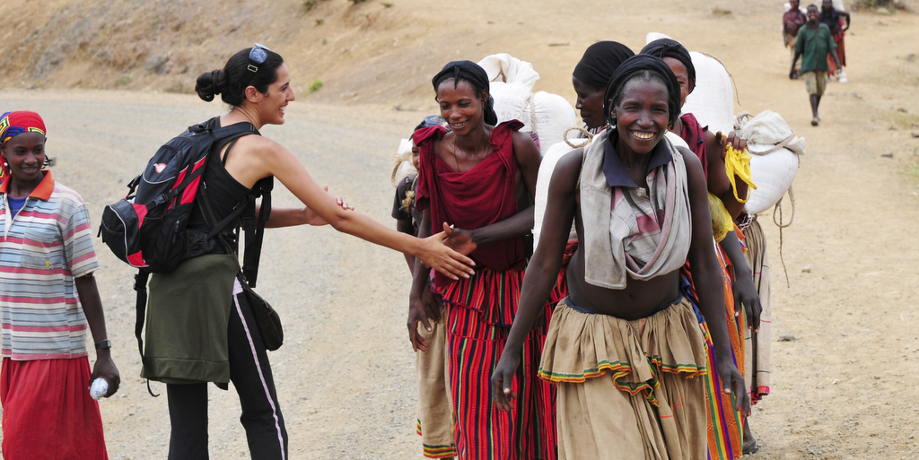 An Israeli woman traveling in Ethiopia greets local villagers with a culturally correct handshake, in which one's left hand rest on the inside of the elbow during the handshake. Konso, Ethiopia